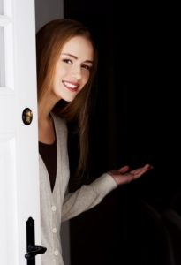 photo of woman inviting one into her front door